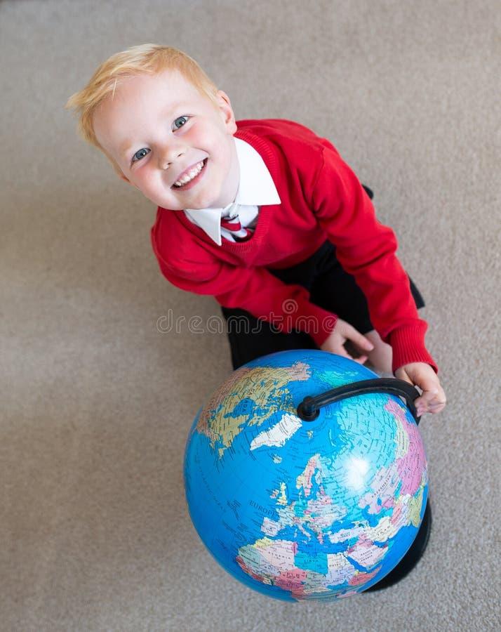 Szczęśliwy dzieciak uśmiecha się kulę ziemską i wiruje obraz stock