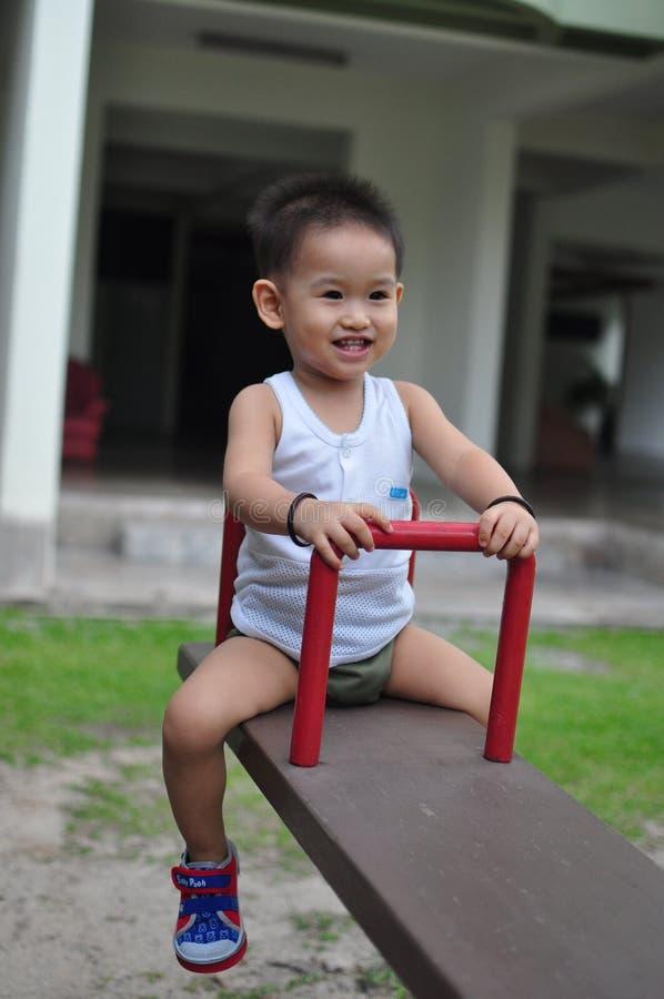 Szczęśliwy dzieciak up up z seesaw obrazy royalty free