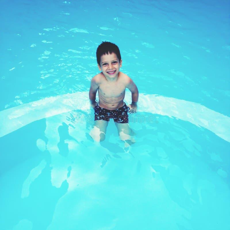 Szczęśliwy dzieciak w pływackim basenie fotografia stock
