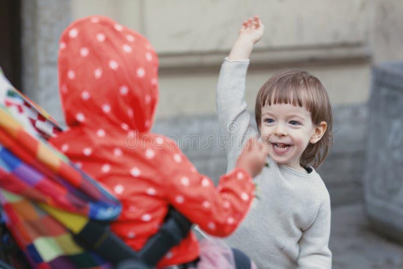 Szczęśliwy dzieciak z długim blondynem bawić się z dziewczyny obsiadaniem w wózku spacerowym troszkę zdjęcie stock