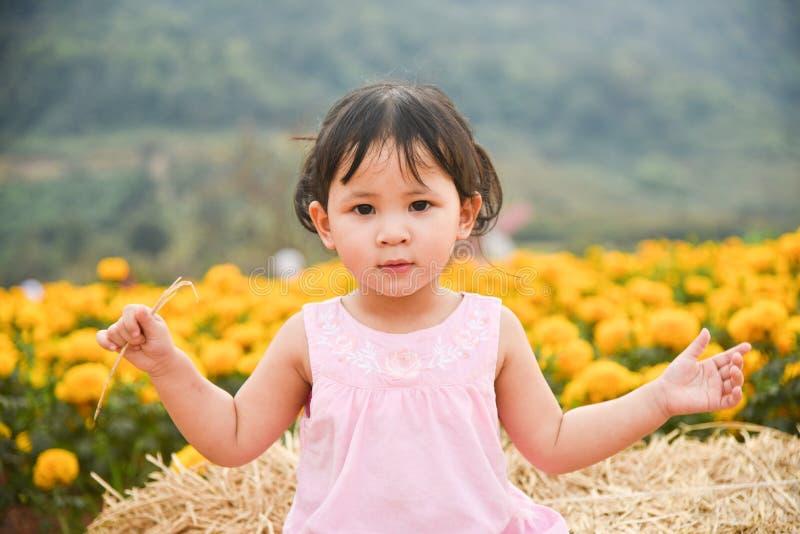 Szczęśliwy dzieciak z wiosna nagietkiem kwitnie kolor żółtego obraz royalty free