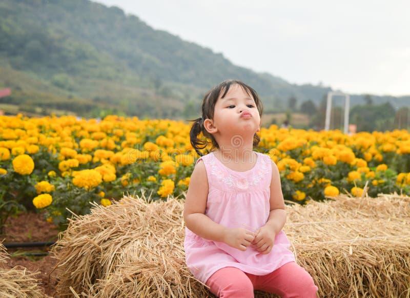 Szczęśliwy dzieciak z wiosna nagietkiem kwitnie kolor żółtego obraz stock