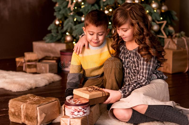 Szczęśliwy dzieciaka brat, siostra i jesteśmy biorąc pod uwagę prezenty, fotografia stock