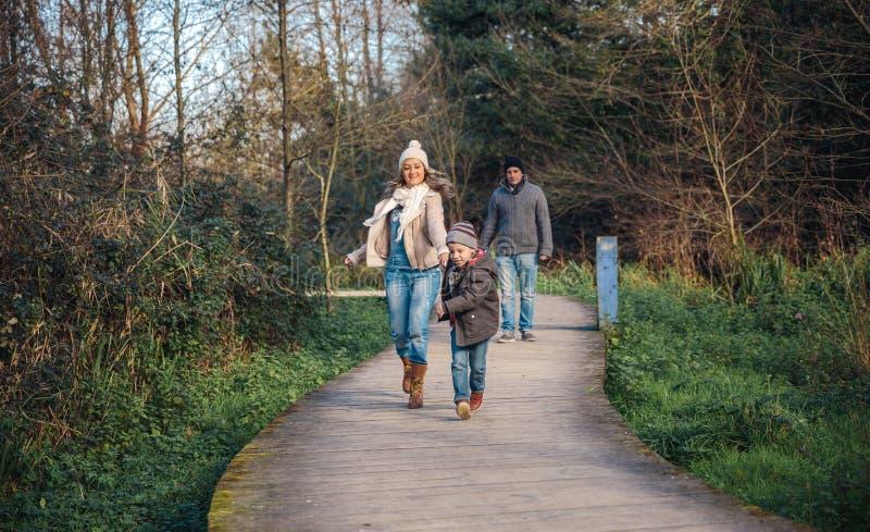 Szczęśliwy dzieciaka i kobiety bieg w lesie zdjęcia royalty free