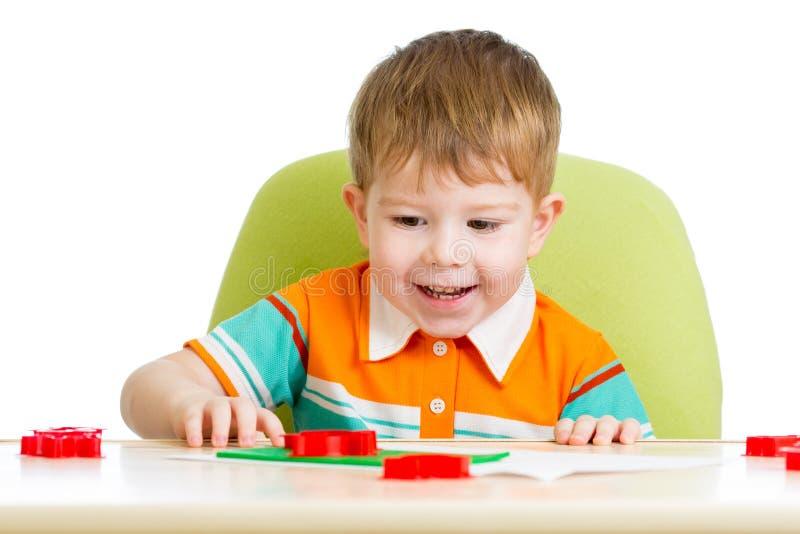 Szczęśliwy dzieciaka obsiadanie przy stołowym i bawić się obrazy stock