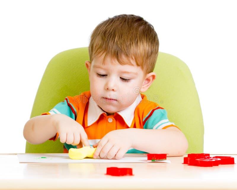 Szczęśliwy dzieciaka obsiadanie przy stołowym i bawić się obraz stock
