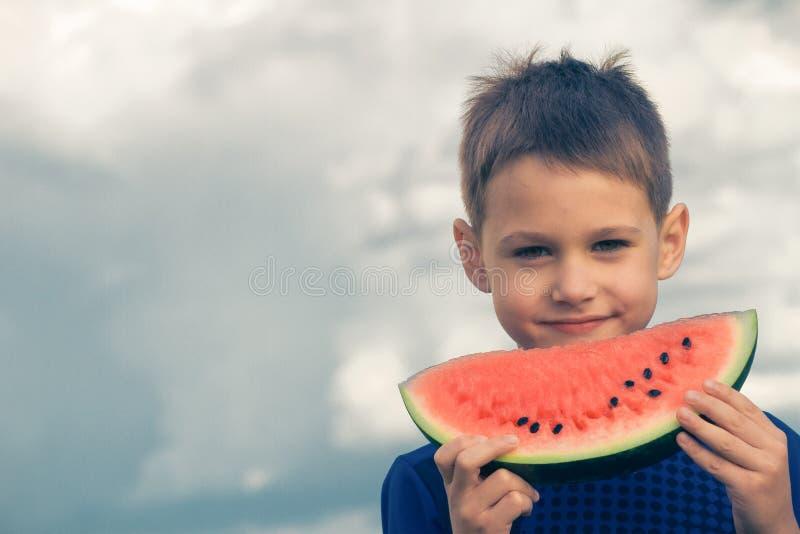 Szczęśliwy dziecka łasowania arbuz outdoors obraz stock