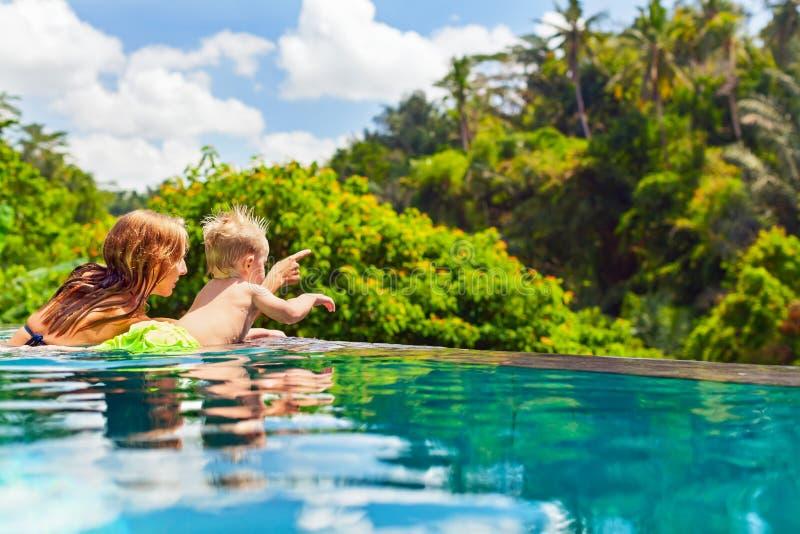 Szczęśliwy dziecka dopłynięcie wewnątrz z macierzystym nieskończoność basenem fotografia royalty free