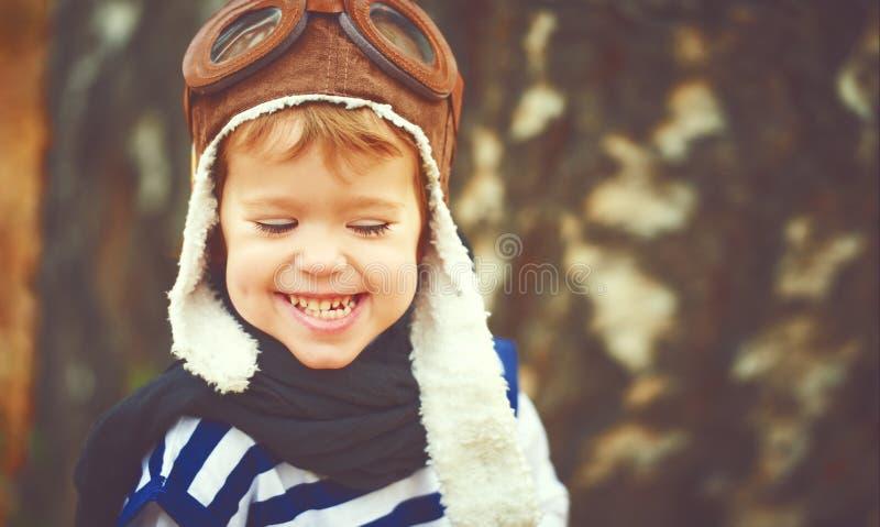 Szczęśliwy dziecko bawić się pilotowego lotnika outdoors w jesieni obraz stock