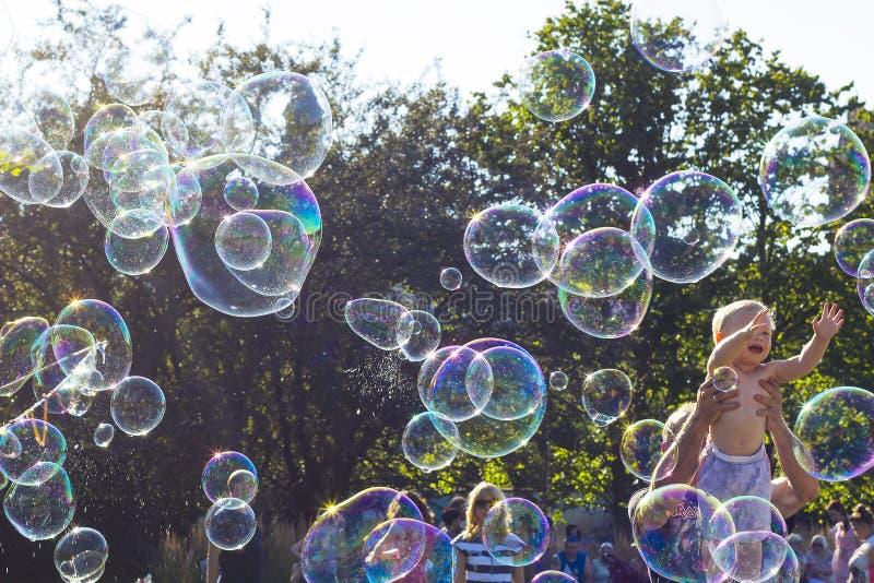 Szczęśliwy dziecko bawić się z mydlanymi bąblami przeciw niebieskiemu niebu fotografia royalty free