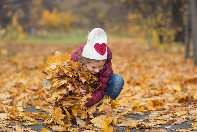 Szczęśliwy dziecko, dziewczyna trzyma naręcze jesień żółci liście fotografia royalty free