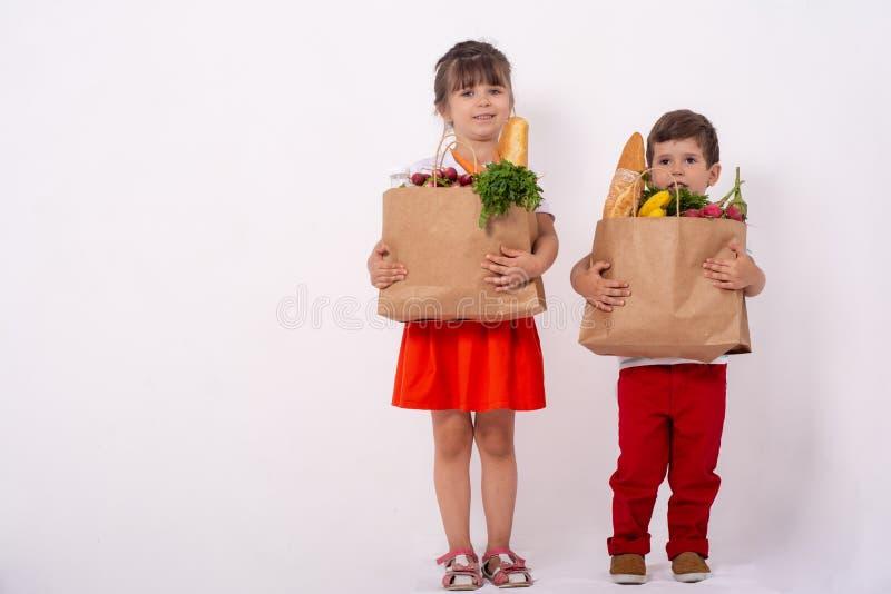 Szczęśliwy dziecko i wózek na zakupy Dzieciaki kupuje jedzenie przy sklepem spożywczym lub supermarketem Dzieci z warzywami, chle zdjęcia royalty free
