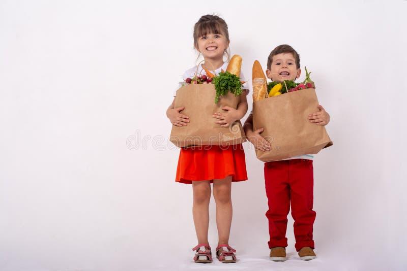 Szczęśliwy dziecko i wózek na zakupy Dzieciaki kupuje jedzenie przy sklepem spożywczym lub supermarketem Dzieci z warzywami, chle fotografia royalty free