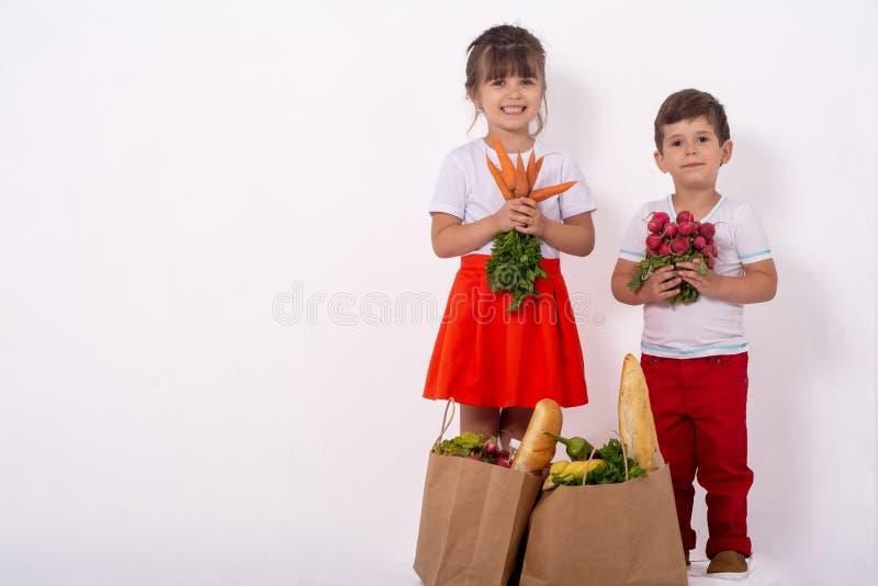 Szczęśliwy dziecko i wózek na zakupy Dzieciaki kupuje jedzenie przy sklepem spożywczym lub supermarketem Dzieci z warzywami, chle obrazy royalty free
