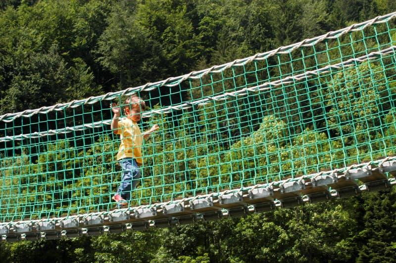 Szczęśliwy dziecko krzyżuje nad zawieszenie mostem fotografia stock