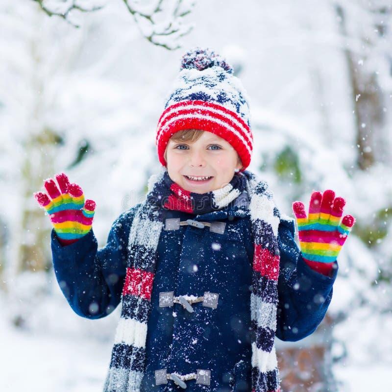 Szczęśliwy dziecko ma zabawę z śniegiem w zimie obraz stock