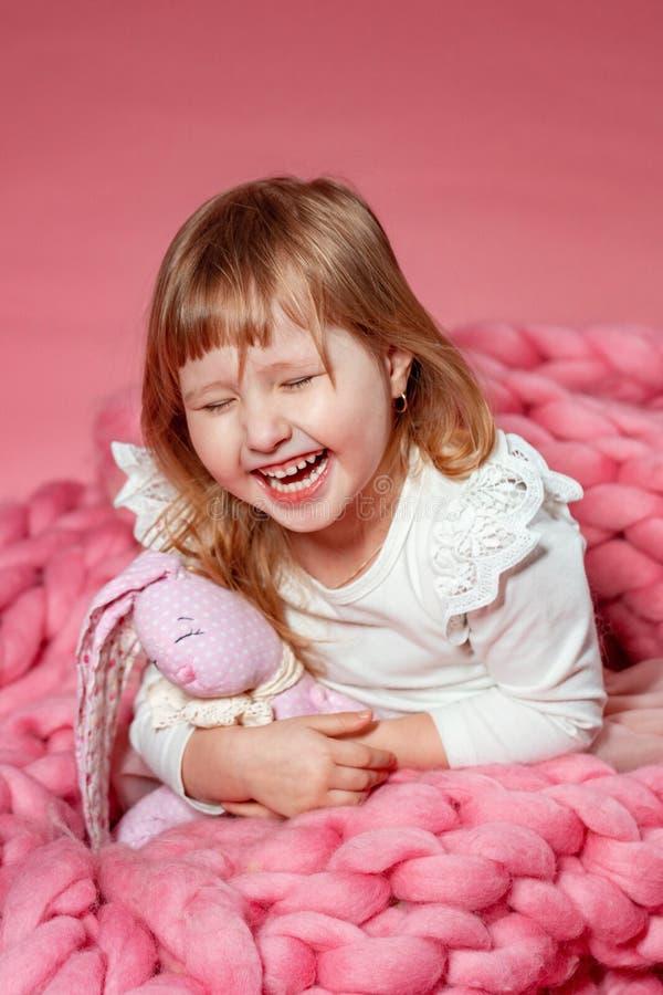 Szczęśliwy dziecko na różowym koralowym tle patrzeje w górę niespodzianki w zdjęcie stock