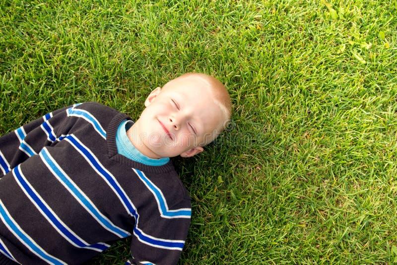Szczęśliwy dziecko na zielonej trawie fotografia stock