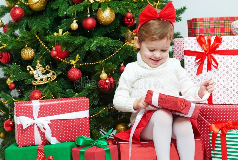 Szczęśliwy dziecko otwiera Bożenarodzeniowych prezenty blisko drzewa obraz royalty free