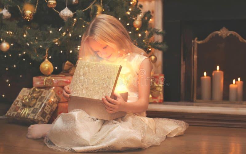 szczęśliwy dziecko otwiera magicznego pudełkowatego prezent z światłem w zmroku nad choinki i graby domem fotografia royalty free