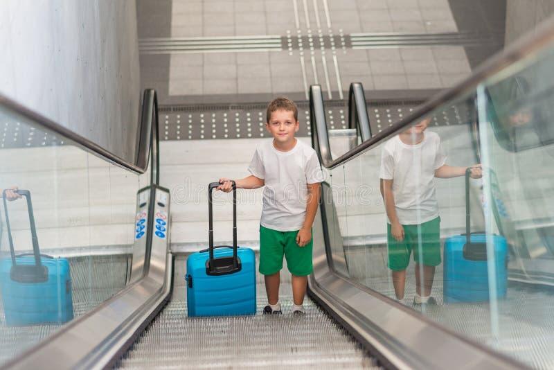 Szczęśliwy dziecko podróżuje i trzyma bagażowy na eskalatorze fotografia stock
