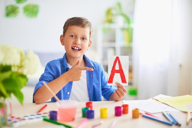 Szczęśliwy dziecko przy stołem z szkolnymi dostawami uśmiecha się śmiesznego i uczy się abecadło w figlarnie sposobie pozytywny u obraz royalty free