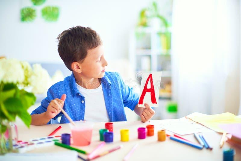 Szczęśliwy dziecko przy stołem z szkolnymi dostawami uśmiecha się śmiesznego i uczy się abecadło w figlarnie sposobie pozytywny u zdjęcia stock