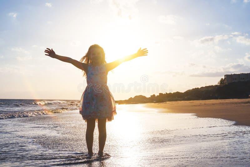 Szczęśliwy dziecko rozprzestrzenia jej ręki na w górę plaży na wspaniałym zmierzchu - dziewczynka ma zabawę w urlopowych wakacjac zdjęcie royalty free
