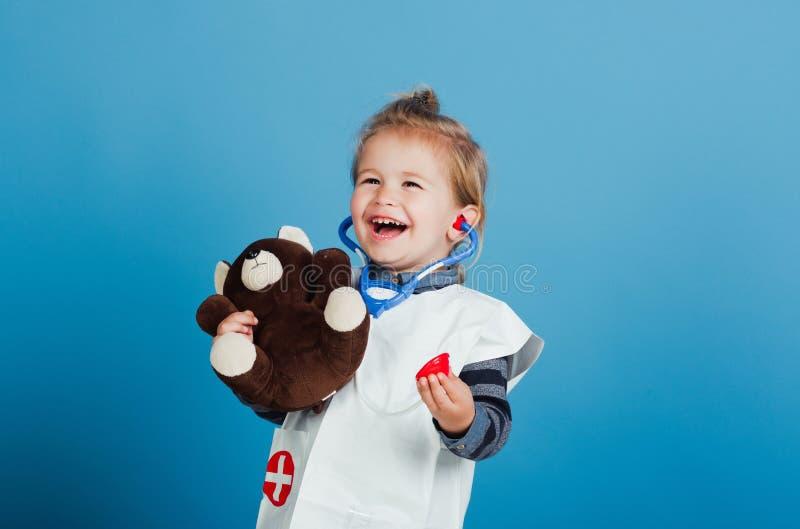 Szczęśliwy dziecko weterynarza uśmiech z misiem na błękitnym tle obraz royalty free