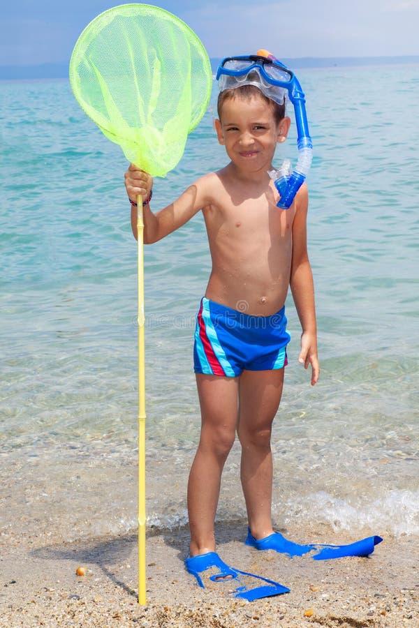 Szczęśliwy dziecko z nurkowym wyposażeniem na plaży obraz stock