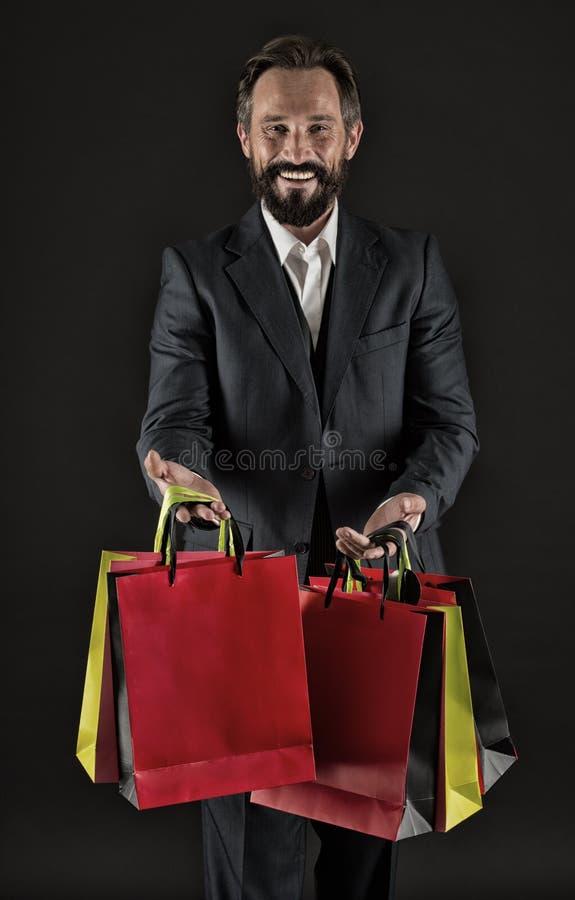 Szczęśliwy dzielić Mężczyzna dojrzały kupujący niesie torba na zakupy czarnego tło Pomyślny biznesmen wybiera tylko luksusowego zdjęcie stock