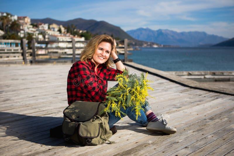 Szczęśliwy dziewczyna podróżnik siedzi na drewnianym molu i trzyma bukiet kwiaty mimozy w rękach zdjęcie stock
