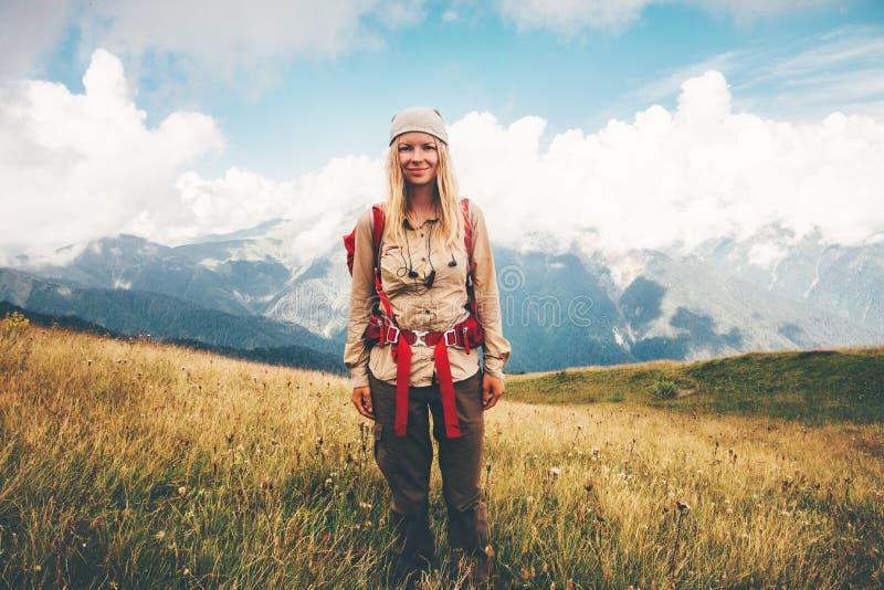 Szczęśliwy dziewczyna podróżnik wycieczkuje przy górami z plecakiem zdjęcie royalty free