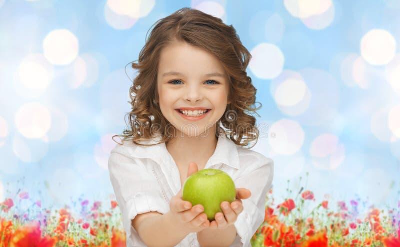 Szczęśliwy dziewczyny mienia jabłko nad ogrodowym tłem obraz stock