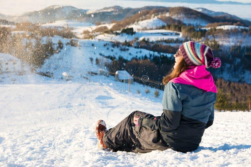Szczęśliwy dziewczyny obsiadanie w śniegu na górze obrazy stock
