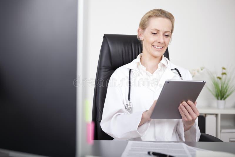 Szczęśliwy Żeński klinicysta Używa jej pastylka komputer obrazy stock