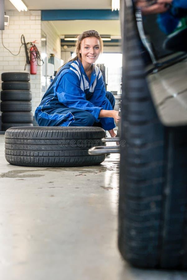 Szczęśliwy Żeński mechanik Zmienia Samochodową oponę Przy samochodu sklepem zdjęcie royalty free