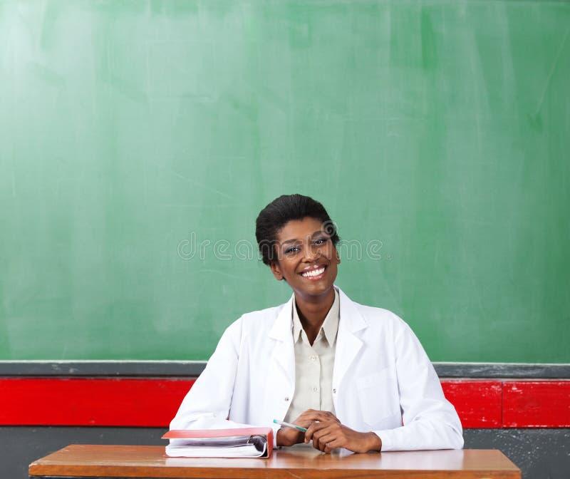Szczęśliwy Żeńskiego nauczyciela obsiadanie Przy biurkiem W sala lekcyjnej zdjęcia royalty free