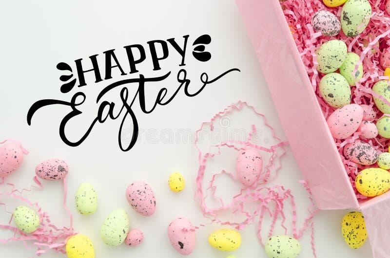 Szczęśliwy Easter ręki literowania kartki z pozdrowieniami projekt Kolorowi Wielkanocni jajka w pudełku na bielu stole, odgórny w fotografia stock