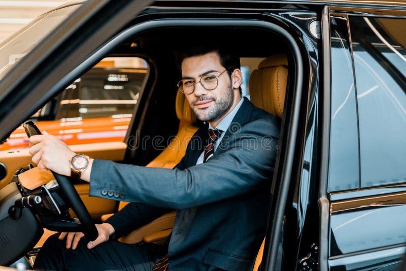 szczęśliwy elegancki biznesmen w eyeglasses siedzieć zdjęcia royalty free