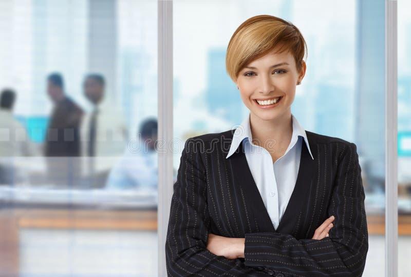 Szczęśliwy elegancki bizneswoman przy biurem obrazy stock
