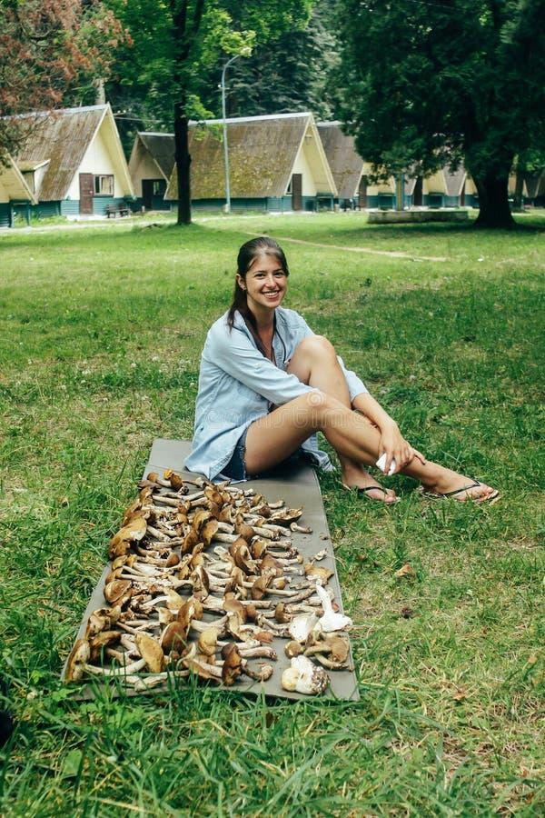 Szczęśliwy elegancki dziewczyna podróżnika obsiadanie przy stosem zbierająca pieczarka obraz stock