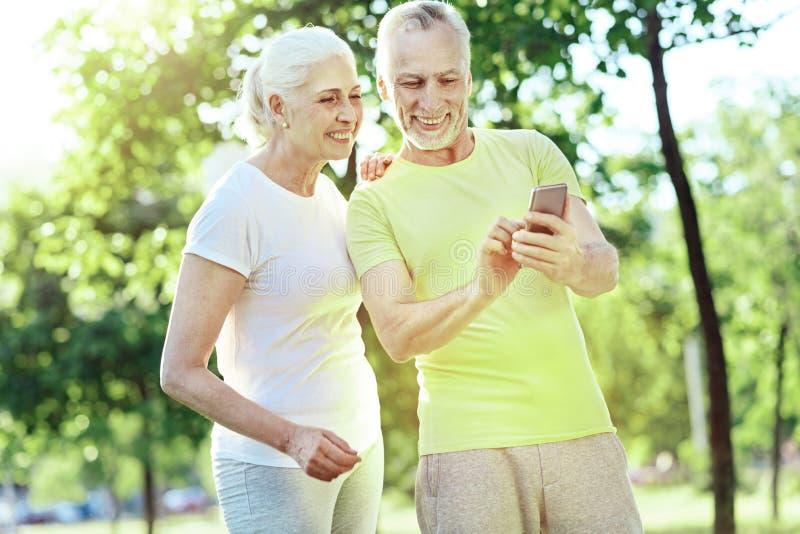 Szczęśliwy emeryt pokazuje smartphone jego żona fotografia stock