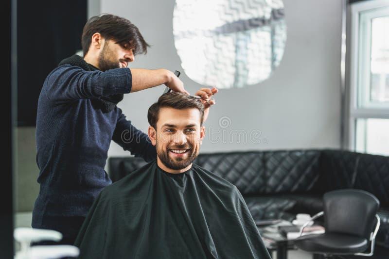 Szczęśliwy facet dostaje ostrzyżenie fryzjerem obraz royalty free