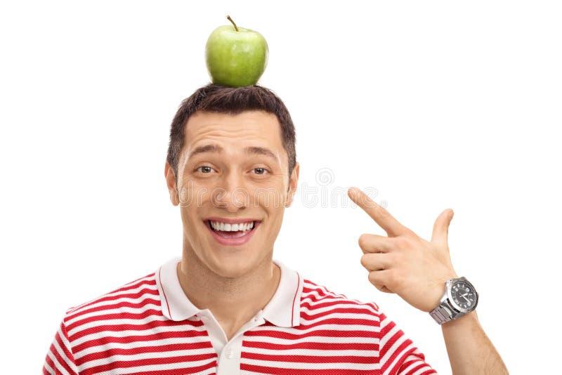 Szczęśliwy facet wskazuje przy jabłkiem na jego głowie obraz stock