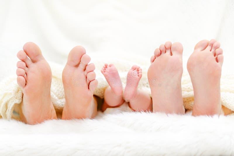 Szczęśliwy familiy w łóżku Macierzyści ojca i dziecka cieki pod koc Drzewne pary nogi fotografia royalty free