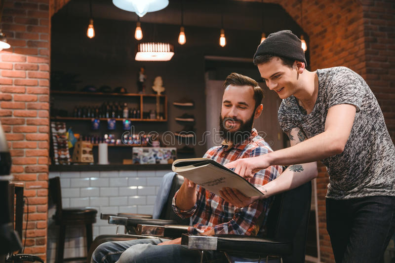 Szczęśliwy fryzjera męskiego i zawartości klient patrzeje przez magazynu zdjęcie royalty free