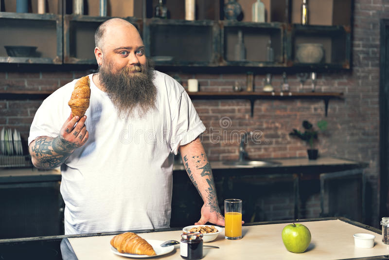 Szczęśliwy gęsty facet ma śniadanie w domu fotografia stock
