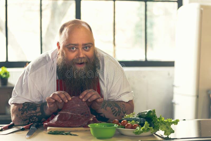 Szczęśliwy gęsty faceta kucharstwo w kuchni zdjęcia royalty free