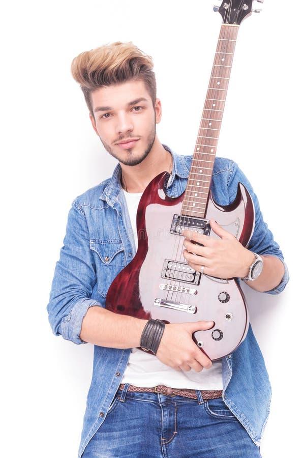 Szczęśliwy gitarzysta trzyma czerwoną gitarę elektryczną w jego ręki obraz royalty free